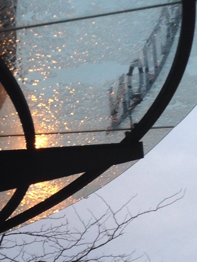 Streetlight shining through raindrops on glass canopy over entrance to Grohmann Museum