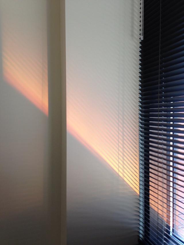 orange light slanting through Venetian blind