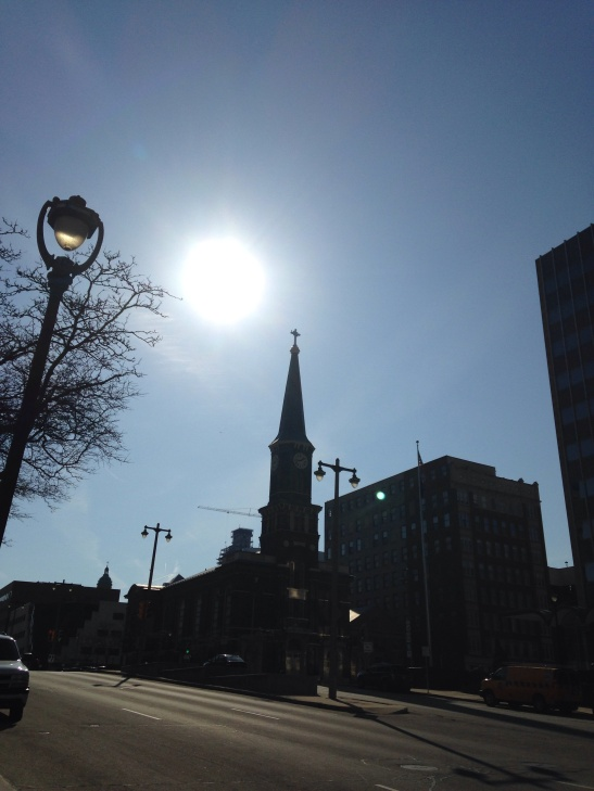church steeple silhouetted against bright sun